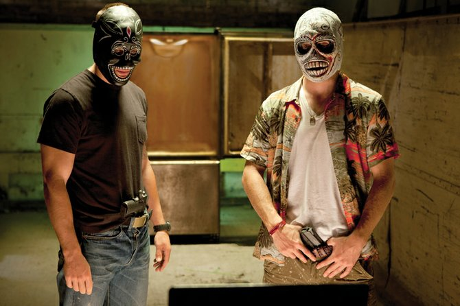 "Drug dealers Chon (Taylor Kitsch), left, and Ben (Aaron Johnson) don Santa Muerte masks as they speak with rival drug peddlers via webcam in ""Savages."" The movie is about two best friends in the marijuana business who are threatened by a Mexican cartel, leading to an escalating war between the two sides."