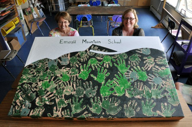Lowell Whiteman Primary School Admissions Director Debbie Gooding, left, and Head of School Sharon Mensing show off a painting students made last month to start embracing the new name of their school.