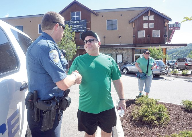 "Boulder resident David Elrod thanks Steamboat Springs Police Department officer Evan Driscoll as he leaves the 1 p.m. Friday showing of ""The Dark Knight Rises"" at Wildhorse Stadium Cinemas. Officers are conducting walk-throughs at local movie theaters in the wake of the shooting at the new Batman movie Friday morning in Aurora."