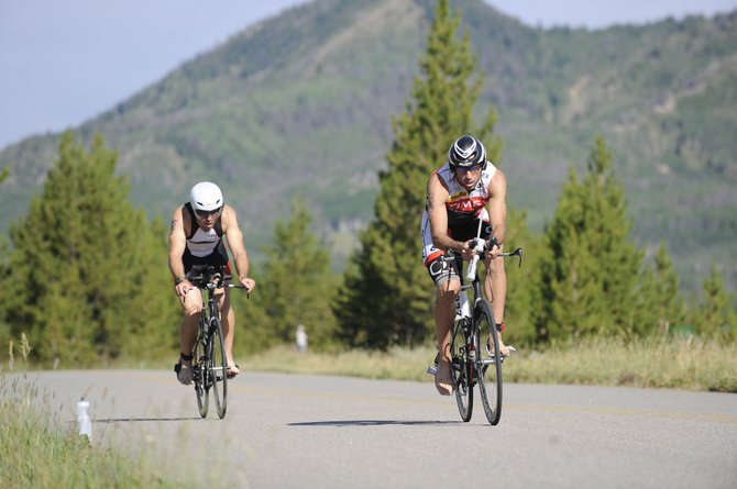 Tim Hola, right, and Chris Clausen speed into the transition area Sunday at the Steamboat Sprint Triathlon. Hola was second overall, and Clausen was ninth.