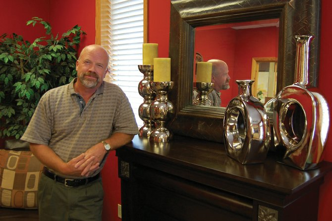 Real estate broker Steve Herman shows off the decorative fireplace in the front office of RE/MAX. Herman, 54, has been with the company for about six years and has lived in Craig for more than 20 years. He enjoys the area's hunting, fishing and other outdoor activities.