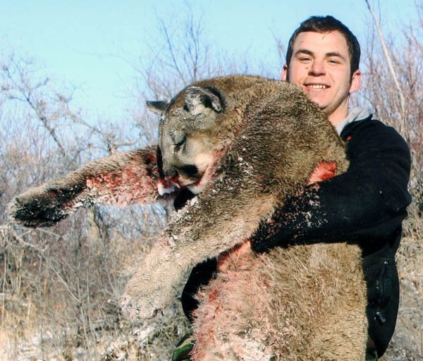Michael Miklavicic holds a mountain lion he shot during a hunting trip last winter.