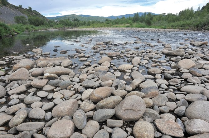 Rocks normally covered by flowing waters sit exposed on the banks of the Yampa River on Tuesday afternoon. Despite recent rains and conservation, the river level on the Yampa remain low.
