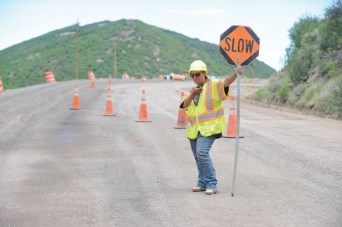 Construction worker Betty Elder directs traffic through a construction area on Routt County Road 131 on Friday afternoon just outside of Oak Creek. The work is expected to be completed by mid-November.