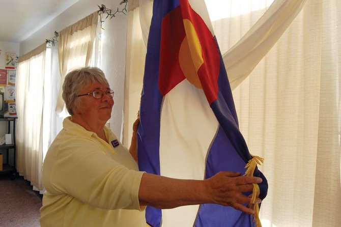 Jo Ann Baxter unfurls the Colorado state flag following a Tuesday morning visit with the Craig Rotary Club. Baxter, a Democrat, spoke to the group about her campaign for state representative for Colorado House District 57.