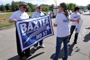 Jo Ann Baxter, right, holding the banner, is a Craig resident and candidate for Colorado House District 57. She is shown here campaigning with her husband, Brian, on Saturday during the Silt Heyday in Garfield County. Baxter has been campaigning for the office in recent weeks in Moffat, Rio Blanco and Garfield counties.