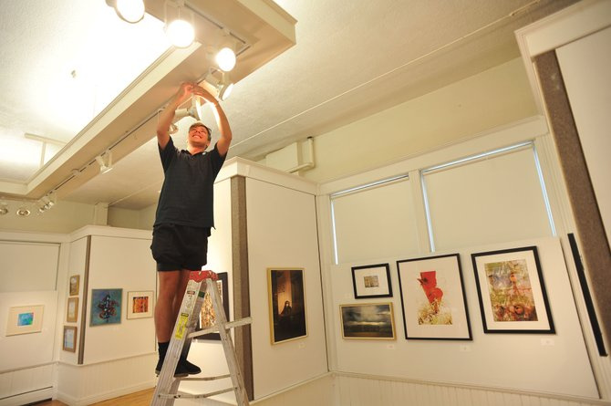 Park Myers, artistic director of the Steamboat Springs Arts Council, adjusts lights for an upcoming art show at the Depot Art Center. The Summer Art exhibit — featuring the work of 25 artists, all of whom are Arts Council members — will be on display this month.