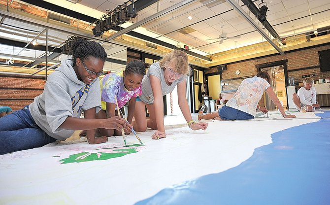 Sophie Camara, Fena Metzler and Eloise Borden work on a mural inside the Depot Art Center as part of a youth program run by the Steamboat Springs Art Council. The City Council approved the first reading of a new lease that will allow the nonprofit to stay in the century-old building and continue to pay $1 per year in rent to operate there.