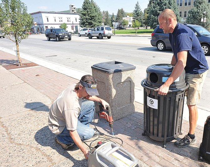 Frank Becker, right, and George Avgares install one of 22 new recycling cans along Lincoln Avenue on Wednesday morning as part of a Leadership Steamboat project. The cans, sponsored by local businesses, are part of an effort to make Steamboat a little greener and protect the scenic beauty of the area.
