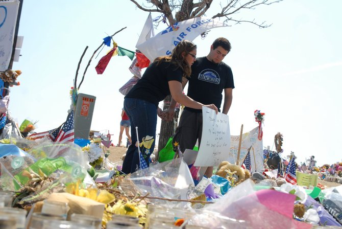 "Jacque Archuleta, 24, a Craig native and Englewood resident, and her boyfriend, Alex Espinoza, visit memorials Friday near the Century Aurora 16 multiplex, the scene of one of the worst shootings in U.S. history. The couple was in theater 9 when a gunman opened fire during a midnight screening of ""The Dark Knight Rises."""