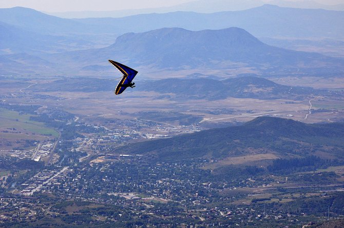 Dean Miller hang glides high over the Yampa Valley on Sunday. Miller and a group of other gliders launched off of Storm Peak.