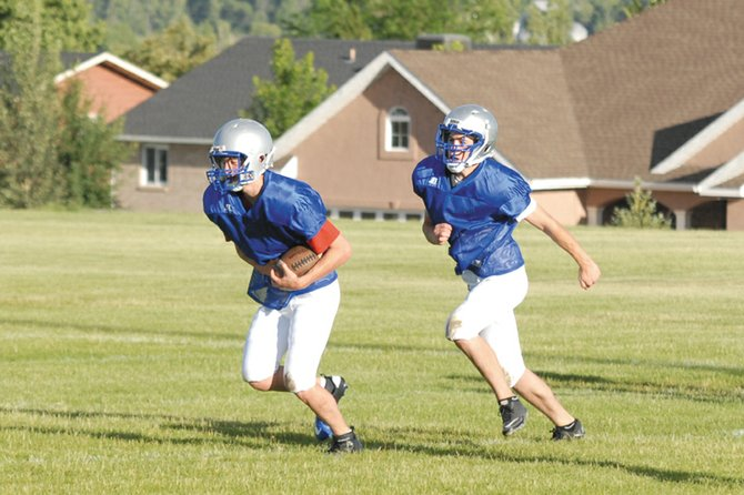 Football players run drills at team camp earlier this summer. Players will be able to put helmets and pads back on this week for the first time since June, as practices for fall season sports at MCHS got under way today.