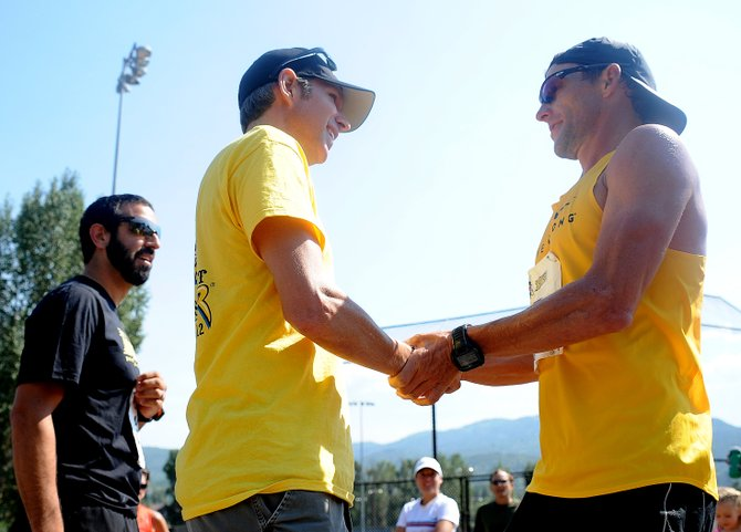 Len Zanni, left, and Lance Armstrong shake hands after Armstrong crossed the finish line in first place at the Steamboat Stinger trail marathon.