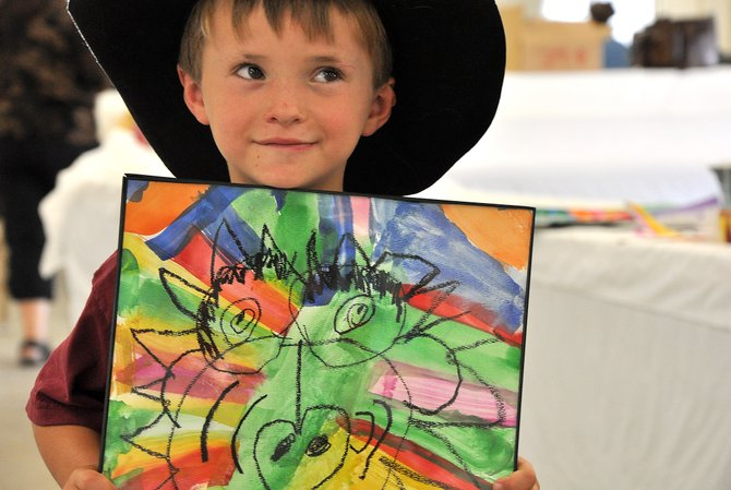 Parker Ashley, of Yampa, shows off his lion painting Wednesday during the check-in day at the Routt County Fair. Entries ranging from Lego masterpieces to large zucchini were streaming into the fairgrounds' Exhibit Hall all afternoon.