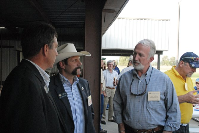Jerry Nettleton, right, environmental manager at Twentymile Mine, chats Tuesday with state representatives Jerry Sonnenberg, left, and Randy Baumgardner, center, during the Colorado Coal & Power Generation Conference barbecue at Loudy-Simpson Park. On Tuesday morning Nettleton updated more than 70 people attending the conference about Twentymile's future expansion into the Sage Creek reserve.