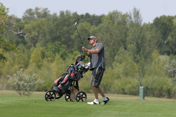 Dan Brown hits an approach to the 18th green at Yampa Valley Golf Course. Brown repeated as men's club champion at YVGC by shooting 72 Saturday and 76 Sunday to win by six strokes, his second title in a row.
