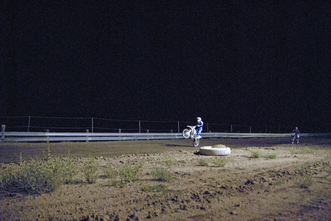 A motocross driver pops a wheelie Saturday night at Thunder Ridge Motorsports Park during the motocross race. It was the first motocross event at Thunder Ridge this summer.