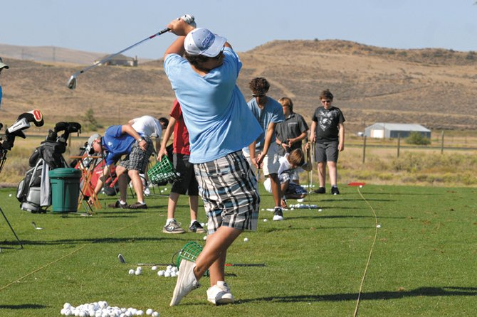Senior Jake Bingham hits from the driving range at Yampa Valley Golf Course. Bingham and the Moffat County High School boys golf team played four tournaments in the first eight days of their season, and now have time to work on their swing before the next tournament Aug. 28.
