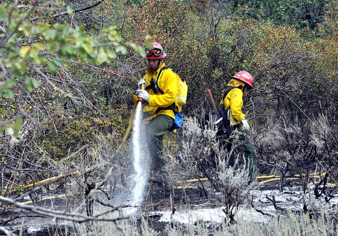 Steamboat Springs Fire Rescue firefighters Christian Keller, left, and Marnie Smith work Monday afternoon to put out the hot spots of a wildfire that grew to half an acre on property in the Elk River Estates. The fire did not reach any structures.