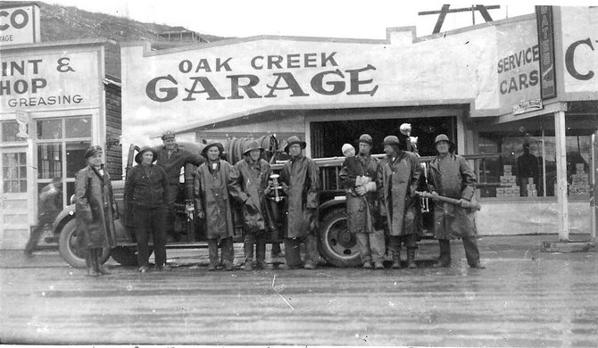 Oak Creek's 1938 fire department volunteers stand in front of the town's original 1937 fire truck. The engine will be featured in the parade Monday.