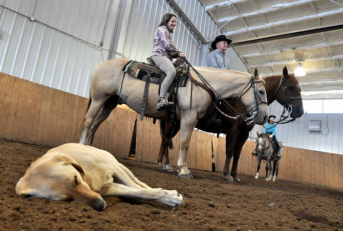 Trooper takes a nap Thursday as Colleen Russo, left, and Patrick King listen to a horse riding lesson inside the indoor practice arena of the Vista Verde Guest Ranch. The ranch was voted the top winter dude ranch and the top dude ranch for kids on a national website.
