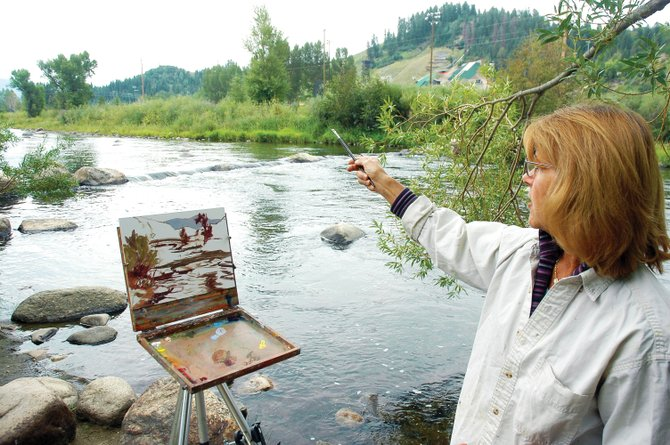 Bonnie McGee points out nuances in the landscape she aims to capture while plein air painting this summer at the Yampa River. McGee is one of four founding members of a new group, the Steamboat Springs Plein Air Painters, which aims to foster the growth of an outdoor painting culture in Steamboat. The four will present their work at a September art show at the Artists' Gallery of Steamboat.