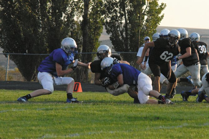 Moffat County High School defenders gang tackle a player from Coal Ridge High School in the backfield during the team's scrimmage last week. The Bulldogs will play their first regular season game of 2012 against Ridge View Academy at noon today at the Bulldog Proving Grounds.