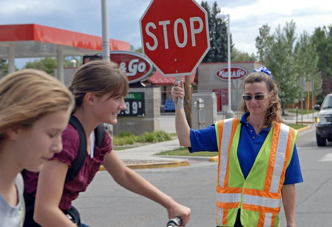Crossing guard Ruth Bell stops traffic Friday at the corner of Colorado Highway 13 and E. Ninth St. near Craig Middle School. Next year the City of Craig will put more than $180,000 in Safe Routes to School grant money to construct sidewalks near the CMS and Sandrock Elementary School campuses.