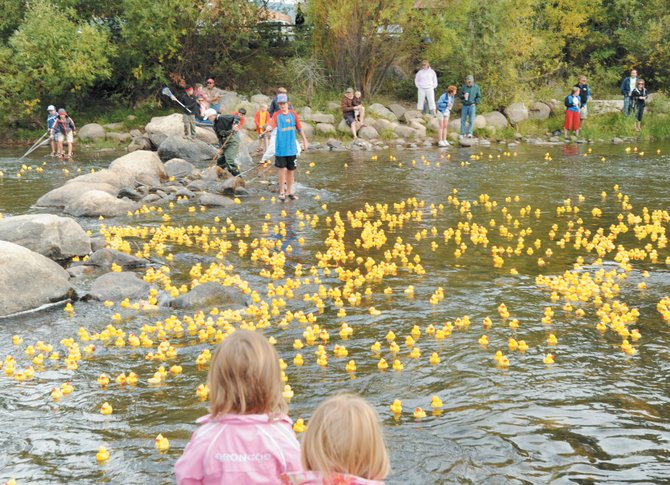 Children help usher a flock of ducks downstream in the Yampa River at the 2009 Rubber Ducky Race in Steamboat Springs.