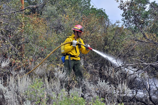 Steamboat Springs Fire Rescue firefighter Christian Keller mops up after a wildfire at the Elk River Estates last month. The Steamboat Springs City Council on Tuesday night was receptive to a plan to give firefighters pay increases next year.