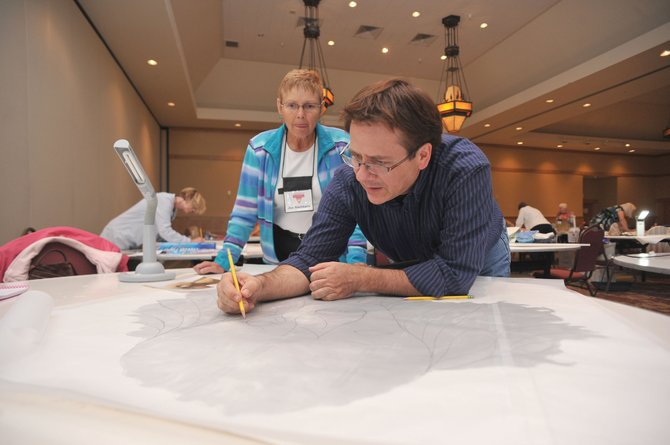 Art quilter David Taylor works with Jan Smithson on her quilt Wednesday afternoon at The Steamboat Grand. Taylor is leading a workshop with about 25 students from across North America who traveled to Steamboat this week to learn about his signature style.