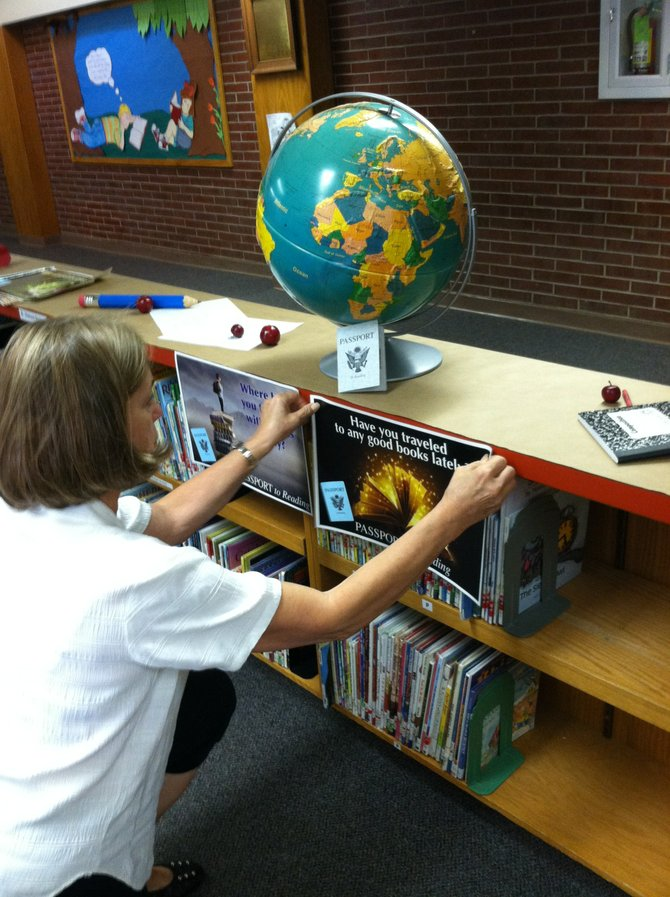 "Librarian Bonnie Thompson, of Sunset Elementary School, hangs a sign and sets up a display in anticipation of the Passport to Reading program. The program, for fourth and fifth graders, aims to encourage students to read books from different genres, and not just ones they are comfortable with. Upon reading books, students receive stamps in their ""passports."""