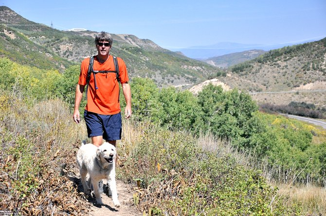 South Routt parent Russ Garrity and his dog, Cayman, walk on the trail behind Garrity's house that Soroco teachers are using to train for the 100-mile Run Rabbit Run race that starts Friday.