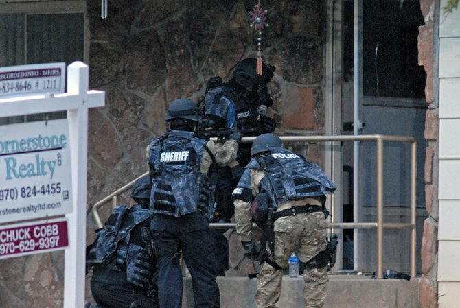 Members of the joint Craig Police Department and Moffat County Sheriff's Office Special Response Team prepare Monday to enter the home of Craig resident Geoffrey Ward Mansfield,39, suspected of being involved in a domestic violence incident. Mansfield barricaded himself in his home at the corner of Rose and 8th Streets, and was taken into custody after a two-hour long standoff with law enforcement officers.