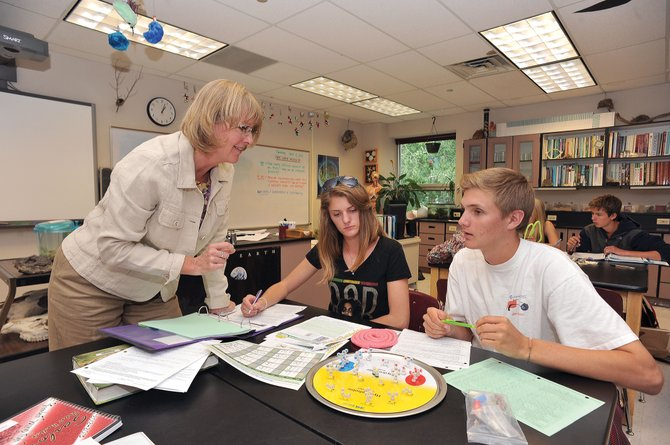 Science teacher Cindy Gay works with students Tari Weekslynn and Quinn Cain during an Advanced Placement biology class Tuesday at Steamboat Springs High School. The Steamboat Springs School District has been accredited with distinction by the state for the third year in a row.