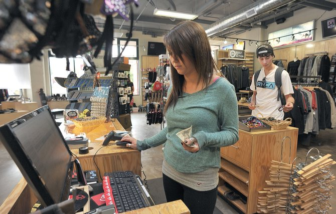 Mara Fling waits on Corey Jacobs at the Quicksilver store in downtown Steamboat Springs on Wednesday afternoon. Yampa Valley Data Partners reports that retail sales were up 12 percent in May in Routt and Moffat counties compared with the same month last year.