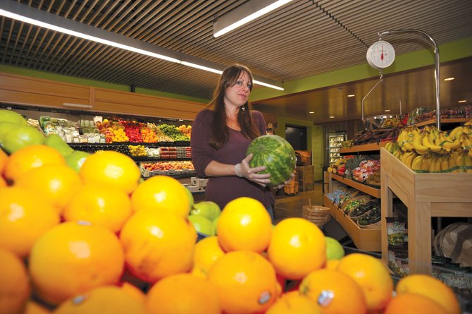 Meghan O'Brien stocks the produce department Thursday at the Natural Grocers by Vitamin Cottage in downtown Steamboat Springs. O'Brien was in town to help set up the new store, which will open its doors Friday.