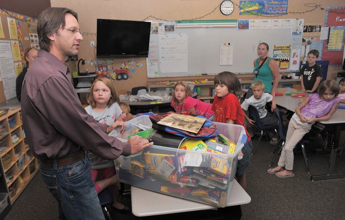 George Avgares, director of the Colorado Student Care Student Learning Center, delivers school supplies to Rebecca Nicholson's third-grade class at Soda Creek Elementary School.