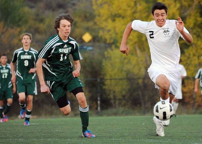 Steamboat's Michael Wong and Summit's Daniel McFadden chase down a ball Thursday during a soccer game in Steamboat Springs. McFadden and his teammates won more battles for loose balls than they lost, helping pave the way to a 1-0 victory for the Tigers.