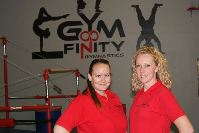 Britany Nielson, left, and Cammy Winder take a break from cleaning to show off their new paint job Thursday inside of Gymfinity Gymnastics. Gymfinity will have its grand reopening from 4-6 p.m. Saturday. Winder and Nielson hope to generate more participation in the gym with its programs for kids.