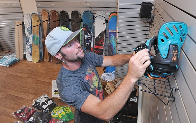 General Manager Torre Saterstrom sets up the inside of Fleischer Sport Ride. The snowboard shop in Old Town Square is the newest location for Fleischer Sport, which also has a store on the mountain.
