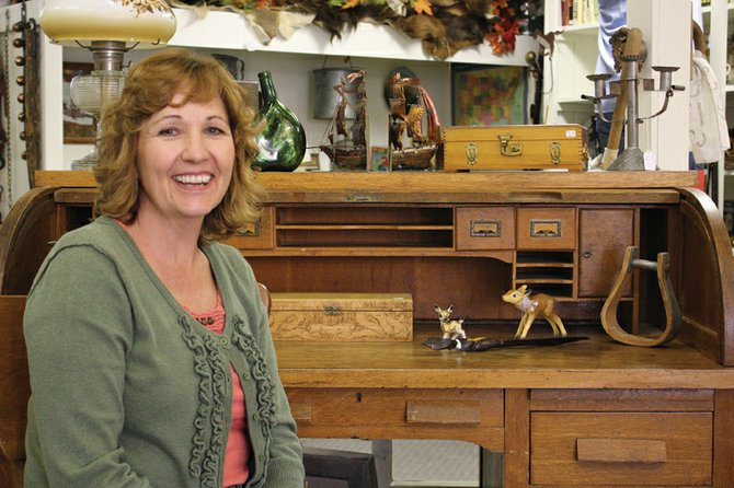 Sherri Fredrickson, co-owner of Favorite Things Antiques, sits at a desk in her store located in Downtown Craig. Fredrickson got her start in the antiques business selling Barbie doll furniture and eventually moved into owning her own store.