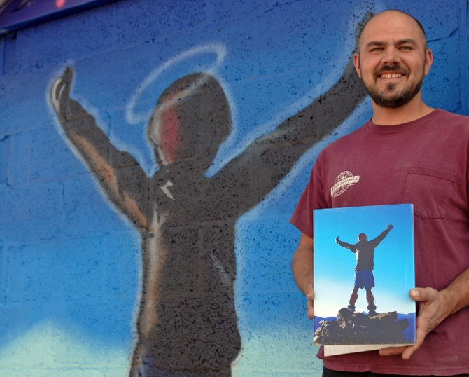 Ryan Otis stands in front of the mural he painted over Labor Day Weekend on the Bear River Young Life Building. A tribute, the mural is based on the photo Otis holds of 25-year-old Jason Kawcak, a Young Life member and leader who died last July in an accident at work.