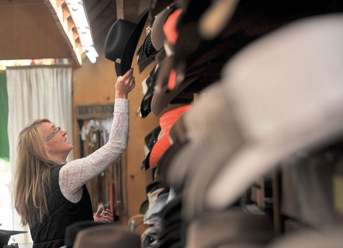 Peggy Pagliaro, floor manager at F.M. Light & Sons in Steamboat Springs, picks out a hat for a customer Wednesday at the historic downtown retail outlet. Lindsay (Lockhart) Dillenbeck and her husband, Chris, now own the longtime family-owned business.