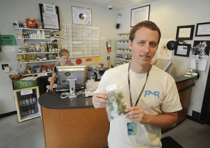 Rocky Mountain Remedies co-owner Kevin Fisher shows what an ounce of marijuana looks like. That is the amount a person would be able to possess legally if voters approve Amendment 64 on Nov. 6.