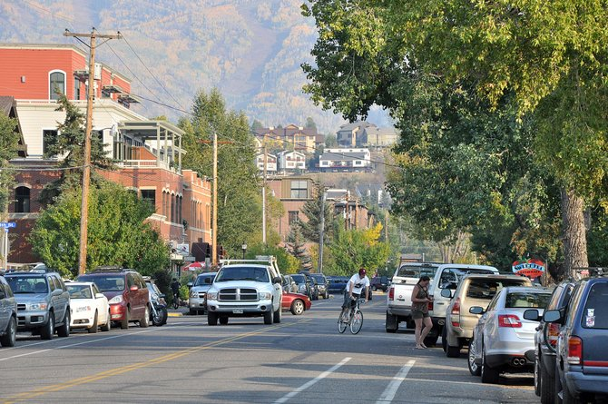 A biker navigates Yampa Street traffic Friday night. Stakeholders on the street are meeting weekly to chart a course to revitalize the pedestrian-busy roadway.