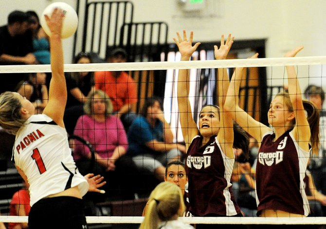 Soroco's Mackenzie Carnahan, left, and Josie Rossi go up for a block Saturday against Paonia. The Rams went point-for-point with the Eagles in a tight first game but couldn't keep it up, falling in three.