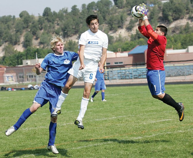 Moffat County goalkeeper Alex Arellano, right, snatches up the ball as Roaring Fork's Dakotah Grett (6) attempts a header and the Bulldogs' Brenden Spencer defends during Saturday's game at Roaring Fork. The ball cleared Grett's head as Arellano hauled it in.