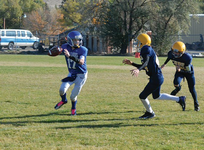 Cole White, No. 17, looks to throw on the run during the Craig Middle School seventh-grade game vs. Rifle Saturday at CMS. White would complete the pass on this play and the Bulldogs rolled to a 38-0 victory.