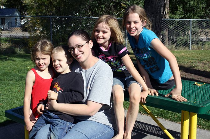 Marissa David, a stay-at-home mom from Craig, poses at a picnic table with her children, from left, Mary, John, Kiersten and Alina.